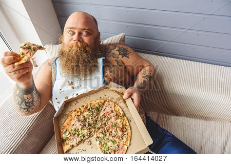 Hungry fat man is holding piece of pizza and looking at it with desire. He is sitting on sofa with relaxation