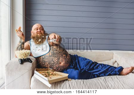Lazy fat man is watching tv at home. He is holding remote control while eating unhealthy food. Fatso is lying on sofa with relaxation