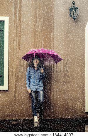 rainy season Woman in jeans and holding a pink umbrella in rainy day.