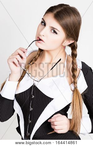 sexy secretary, portrait of beautiful brunette business lady wearing in pinstripe suit biting the handle of glasses.