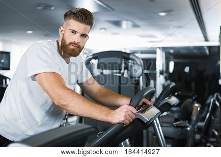 Confident sportsman is sitting at training apparatus and looking at camera with smile