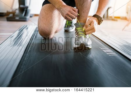 Sportsman is on treadmill, he lacing up his shoe. Close up