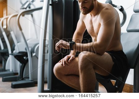 Muscled assured man is sitting at training apparatus. He checking time