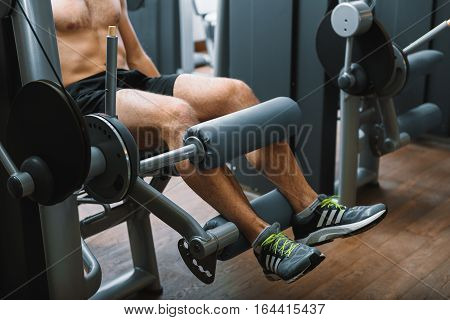 Man is sitting at power training apparatus and taking exercise