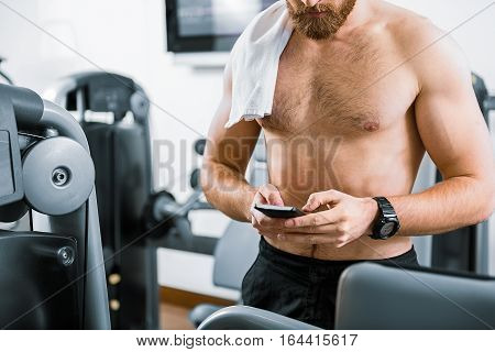 Powerful muscled bearded male person is standing beside apparatus. He typing on his device