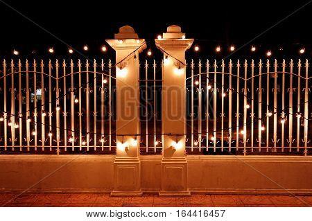 Beautiful night illumination. Light bulbs on the fence.