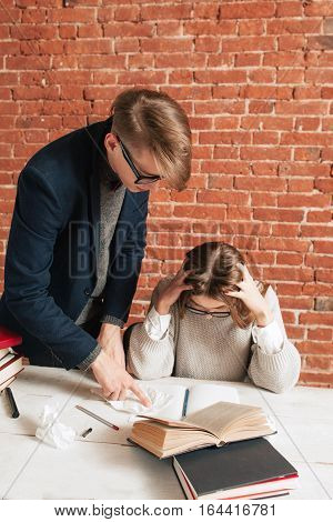 Teacher standing at desk behind tired student. Angry coach explaining mistakes to exhausted girl with headache. Tiredness of education, hard material, too much information concept