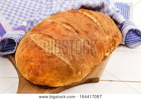 home baked warm bread loaf on a wooden board
