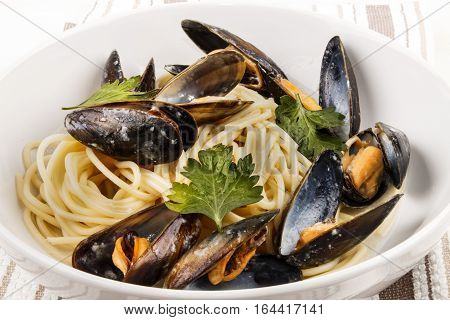 mussel and spaghetti on a deep white plate