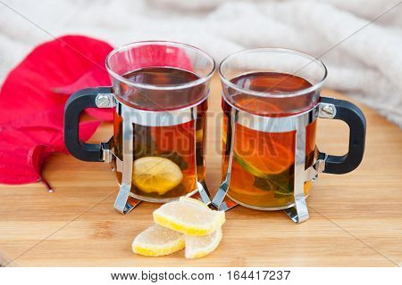 Two glasses of hot black herbal  tea with lime, lemon jellybeans, mint leaves on wooden chopping board on table. Light beige knitted scarf on background. Autumn, winter and christmas concept.