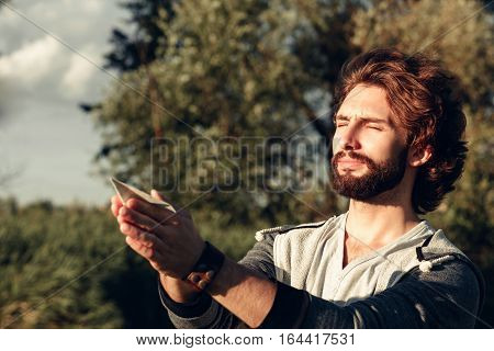 Man praying with paper plane in hands free space. Young guy standing with closed eyes and peaceful expression on face, holding paper airplane. Calm, pacification, relax concept