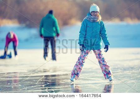 Ice skating. Young girl is skating on a natural frozen lake.