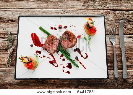 Portion of veal medallions with vegetables flat lay. Top view on white dish with grilled tenderloin, served with asparagus, potatoes and eggplant rolls. Gourmet food, luxury lifestyle concept