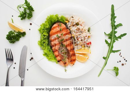 Grilled salmon with rice and cutlery flat lay. Top view on restaurant serving of red fish steak with vegetable risotto. Mediterranean cuisine, seafood menu, healthy food concept