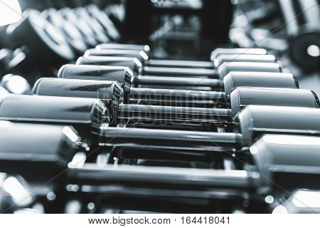Bright luster of small heavy barbells at rack