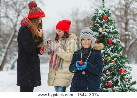 happy children decorating New Year tree with toy balls in park outdoor.