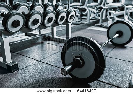 Big heavy barbell with crossbar at floor near rack of dumbbells
