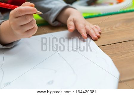 Little Child Drawing With Pencil On White Paper