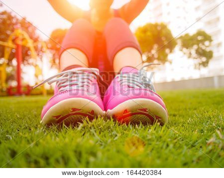 fitness, sport, training and people concept - woman doing abdominal exercises on green grass field with warm light condition and Lens Flare or sunspot