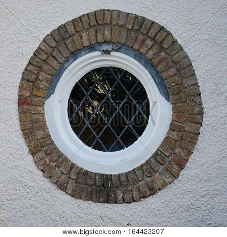 Multi-paned round leaded window inside decorative brick circle in white wall