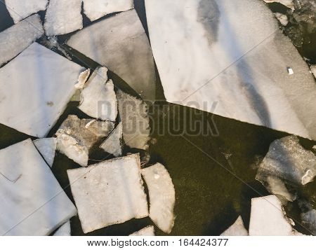 Ice floating on river in spring time. Winter landscape with melting of ice floe. Aerial view.