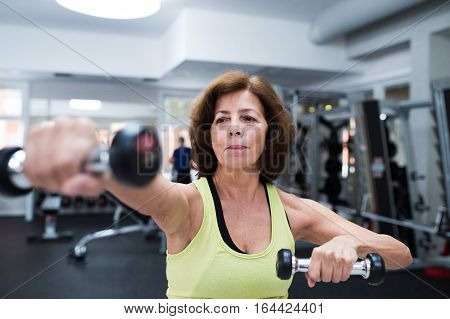 Senior woman in sports clothing in gym working out with weights. Close up of hands. poster