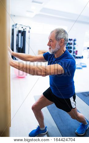 Senior man in sports clothing in gym working out, stretching his legs