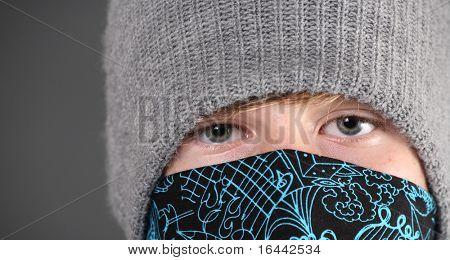 Closeup of a teen boy snowboarder wearing hat and bandanna