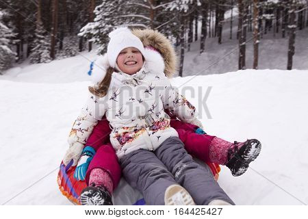 Happy little girl screams with delight rolling with snow hill. Winter fun.