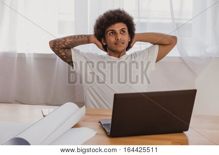 man architect leaning Back On Chair while sitting at his working place in officeTime relax after work done.