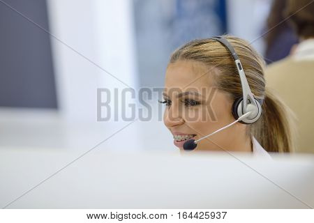 Portrait of a beautiful business woman with braces on the teeth, sitting at the desk and with headphones
