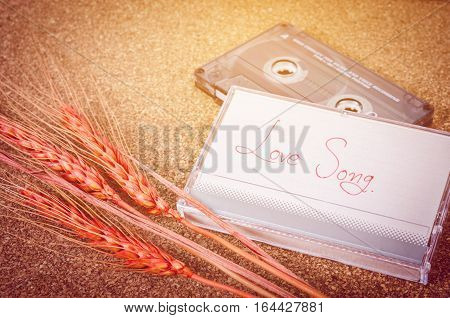 Love song with audio cassette tape on wooden background. Valentine concept.