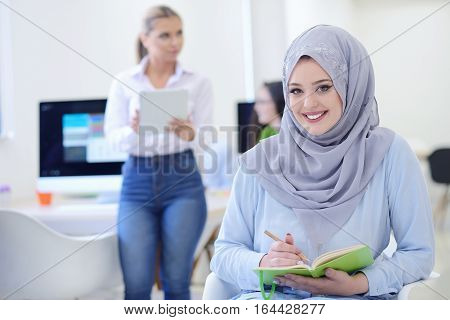 Arabian woman wearing Hijab in office with her colleagues in background