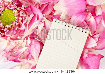 Open blank diary on blooming pink lotus flower background ready for your text.