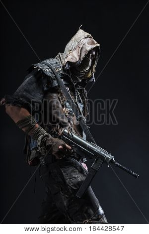 Nuclear post apocalypse life after doomsday concept. Grimy survivor with homemade weapons. Studio closeup portrait on black background