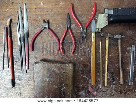 Gold maker tools which are hammer cutter pliers pincers forceps tongs metal file rasp sharpen hone whet halfround file cutter paint brush and wooden plate with trail of melten plastic