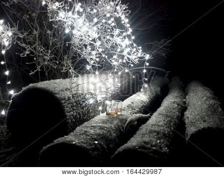 Two whiskey glasses on timber surrounded by lights in winter