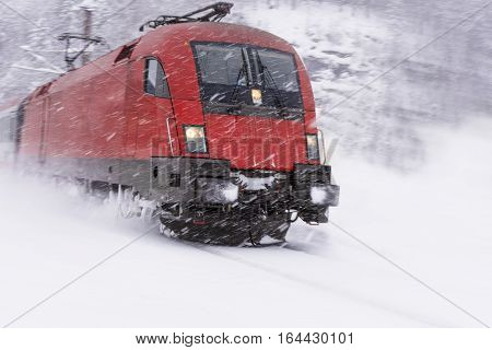Fast Train in Heavy Snow Storm. Blizzard on Railway.