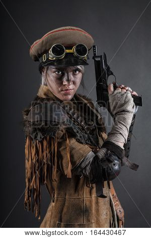 Nuclear post apocalypse life after doomsday concept. Grimy female survivor with homemade weapons. Studio portrait on black background