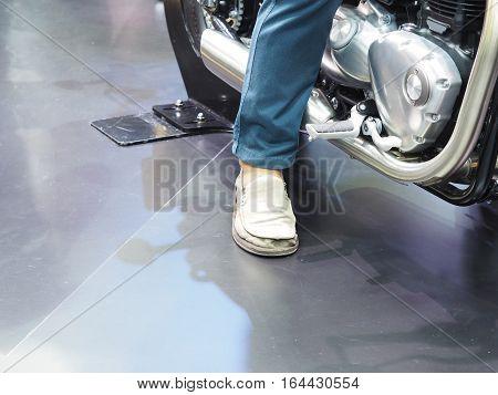 Man's leg on the floor testing motorcycle at showroom.
