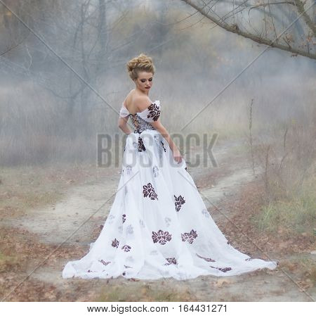 Beautiful young lady in gorgeous vintage white dress in the forest in the fog. Late autumn cold. Melancholy.