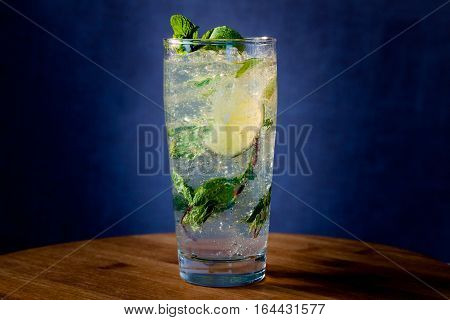 Mojito cocktail with lime, fresh mint and ice in high glass on a wooden table.