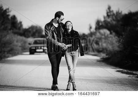 Young happy romantic couple walking along road embracing each other