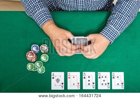 chips and cards for poker in hand on green table top view