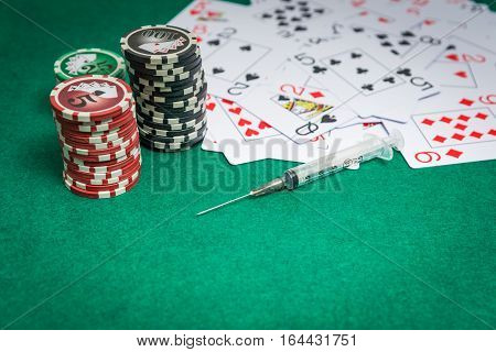 chips cards for poker and syringe. drug concept