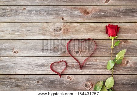 one red rose on wood background with hearts from ribbon. Valentines Day background