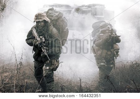 Jagdkommando soldiers Austrian special forces and tank moving on terrain in the fog. They are ready to face the enemy. NATO military power concept
