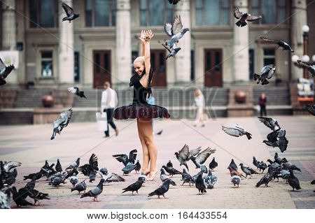 Ballerina posing among birds in the square