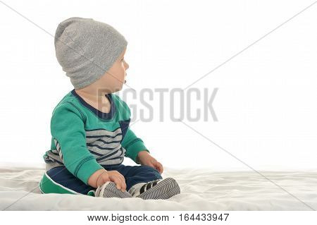 Happy cute baby boy sitting on a white background