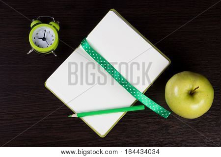 Open notebook with polka dot ribbon and pencil clock and apple on dark wooden background. Different tints of green. Top view. Can be used as a field for notes notebook cover.